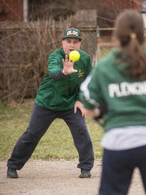 Despite recovering from recent shoulder surgery, Our Lady of Good Counsel softball coach Mike Gerou enthusiastically plays catch with a Crusaders player during practice.