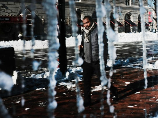 A man is reflected in a frozen window the day after