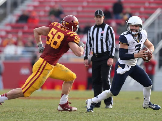 West Virginia quarterback Skylar Howard is flushed out of the pocket by Iowa State right end Cory Morrissey on Saturday, Nov. 29, 2014, at Jack Trice Stadium in Ames, Iowa.