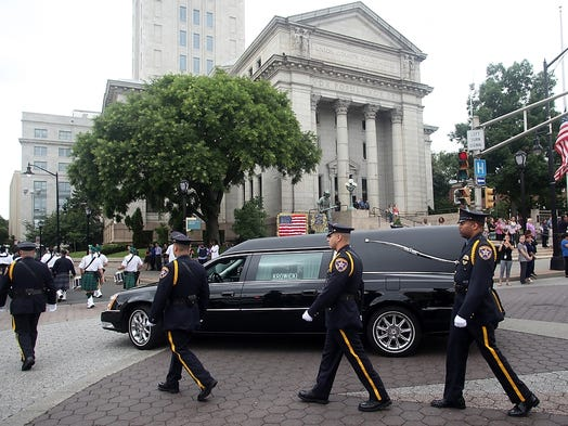 The funeral procession for longtime Union County Sheriff Ralph Froehlich passes the Union County Courthouse, Monday, July 28, 2014, enroute to St. Mary of the Assumption Church in Elizabeth, NJ.   Photo by Jason Towlen