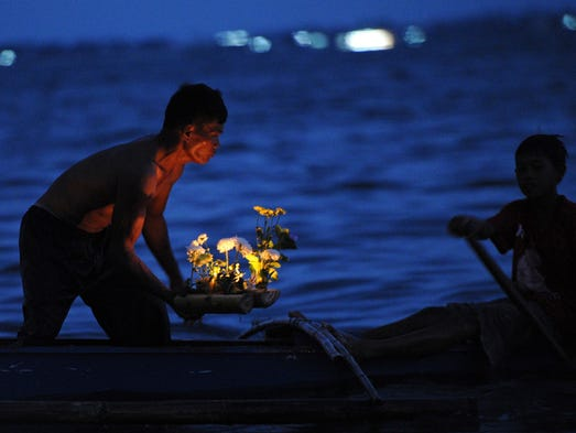 A survivor prepares to launch candle-filled mini boats