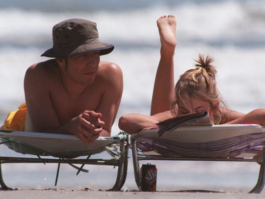 David Saenz, left, and Tiffany Staples, right, both from Three Rivers, enjoy a lazy spring break day on the beach in Port A March 17, 1998.  3/17/98 David Adame