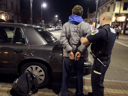 Police handcuff and detain a male after he refused