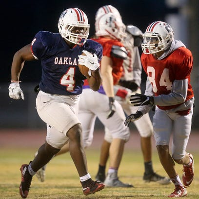 Oakland's Lazarius Patterson (4) runs the ball during