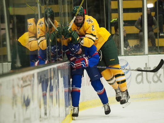 Catamount defenseman Jake Kearley (2) checks Umass-Lowell defenseman Chris Forney (4) into the boards during a college men's hockey game between UMass Lowell and Vermont at Gutterson Fieldhouse on Friday night.