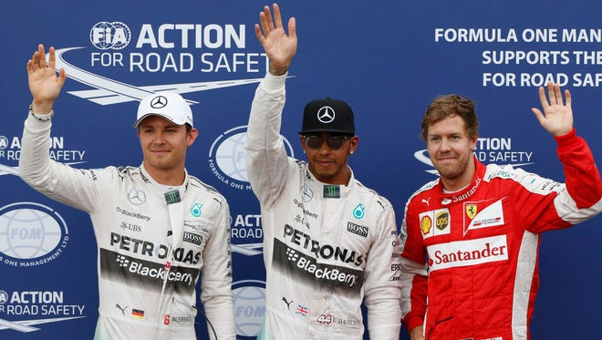 Mercedes driver Lewis Hamilton of Britain gestures after setting the pole position, flanked by his teammate Nico Rosberg of Germany.