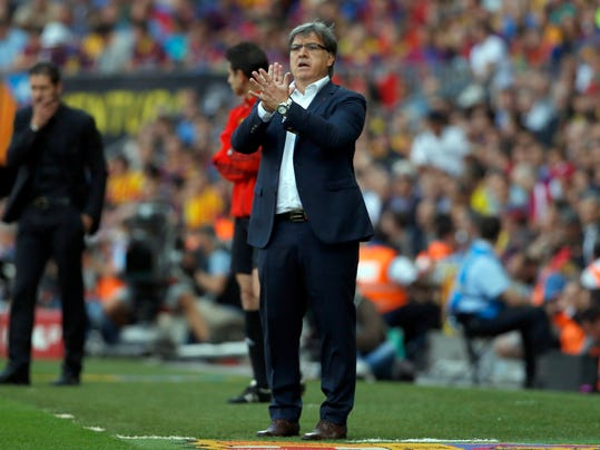 Barcelona's coach Gerardo Martino from Argentina applauds during a Spanish La Liga soccer match between FC Barcelona and Atletico Madrid at the Camp Nou stadium in Barcelona, Spain, Saturday, May 17, 2014. (AP Photo/Emilio Morenatti)