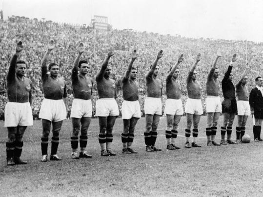 FILE - In this June 19, 1938 file photo, Italian soccer team perform the fascist salute before the start of the World Cup soccer final match against Hungary, in Colombes Stadium, Paris, France. On this day: Italy defended its World Cup crown, beating Hungary 4-2. The tournament took place amid the drumbeat of war. (AP Photo/File)