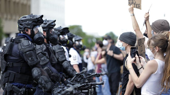 Protesters line up around Columbus Police on the corner of East Board Street and High Street during a George Floyd protest near the Ohio Statehouse in Columbus, Ohio in May 30, 2020.