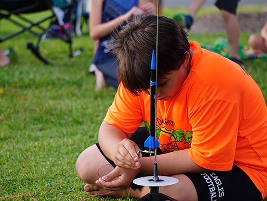 Cub Scout Dillon Kashey preparing his rocket for launch.