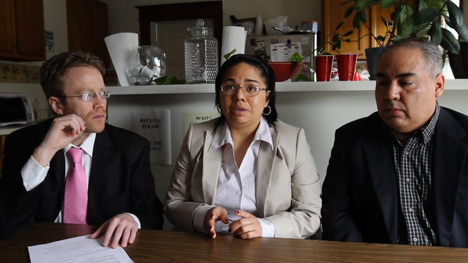 """Maria """"Mia"""" Bocanegra and her husband, Omar Ramos, speak about their lawsuit with Jeremy McLean, who helped with translation at times, at Worker Justice Center of New York in Rochester on May 2, 2014."""
