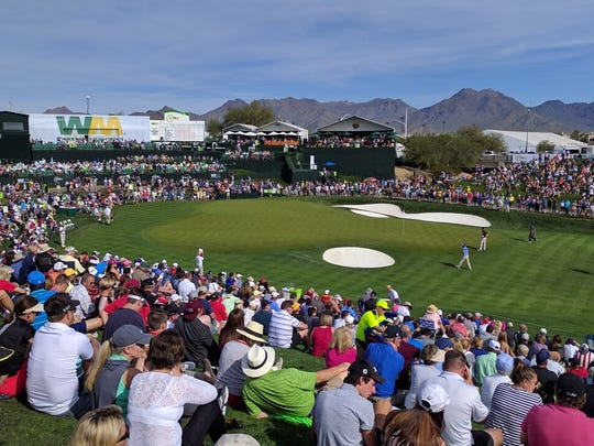 Fans at the 18th hole watch the final round at the