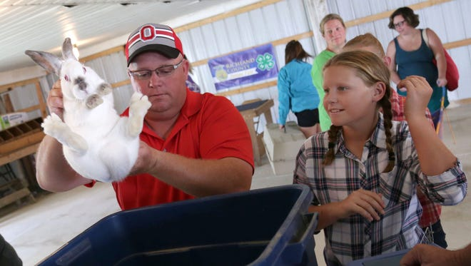 Mike and Taylor Mullins, 11, weigh their rabbits at the Richland County Fairgrounds on Saturday.
