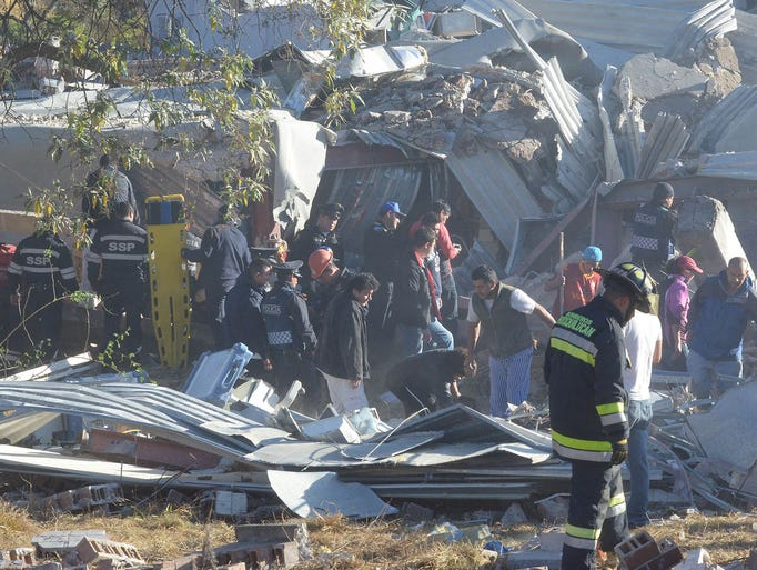 Rescuers work amid the wreckage caused by an explosion