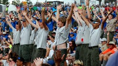 Boy Scouts sing and dance to music as they await the