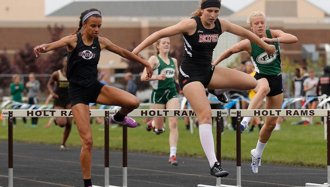 Okemos' Sophia Franklin, left, edges out Rockford's Olivia Rademacher, center, and Forest Hills Central's Cassidy TerHorst, right, for the win in the 300 meter hurdles Friday, May 20, 2016, in Holt, Mich.