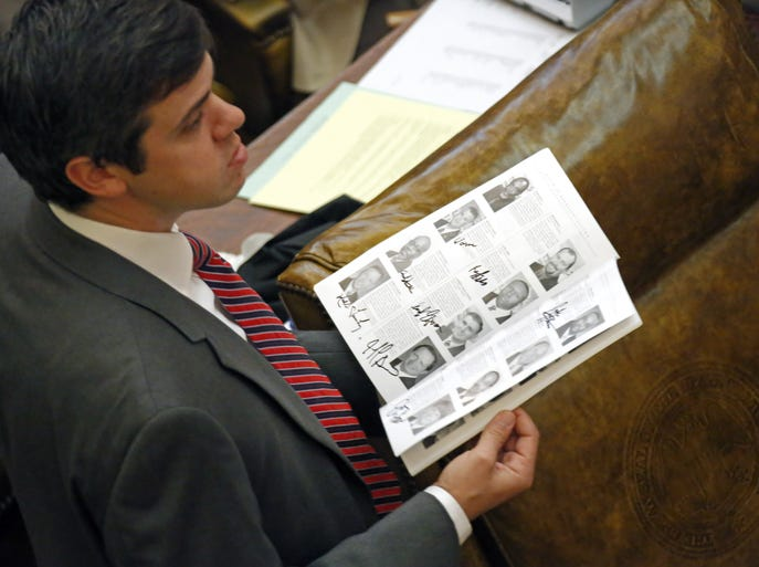 "Republican Rep. Toby Barker of Hattiesburg, looks around for additional lawmakers to sign his legislative roster ""picture book"" as the chamber stood in recess while some procedural work was being considered, Wednesday, April 2, 2014, at the Capitol in Jackson, Miss. Legislators on both sides were attempting to finish out their work early this week so they could conclude the session. (AP Photo/Rogelio V. Solis)"