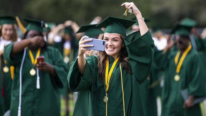 Kennedy Darby records as she turns her tassel after graduating from Forest High School on Tuesday.
