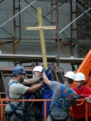 The crew prepares to lift the cross to set it atop the spire of the new Hermance Family Chapel of St. Basil the Great at St. John Fisher College.