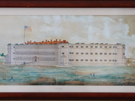 """A painting of Fort Delaware that hangs in the society's board room is showing its age. Society members are worried that if preservation efforts aren't made it will be lost. Among the historical documents showing wear are three """"muster out"""" forms (above, right), a document given out some years after the Civil War had ended. This one is a Pennsylvania document with various scenes of battles in which the unit would have been engaged."""