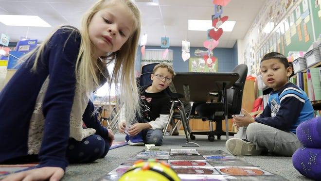 From left: kindergartners Aubrie McElrone, Alexander Piwonski-Dickinson and Lorenzo Monroy-Rodriguez watch a Bee-Bot follow the directions for which they programmed it during class at Hillcrest Elementary School in Hobart on Friday, Feb. 10, 2017. The assignment was part of a new coding curriculum intended to develop digital literacy skills combined with critical thinking and problem solving, which is being introduced to elementary school students in the Pulaski School District this school year.