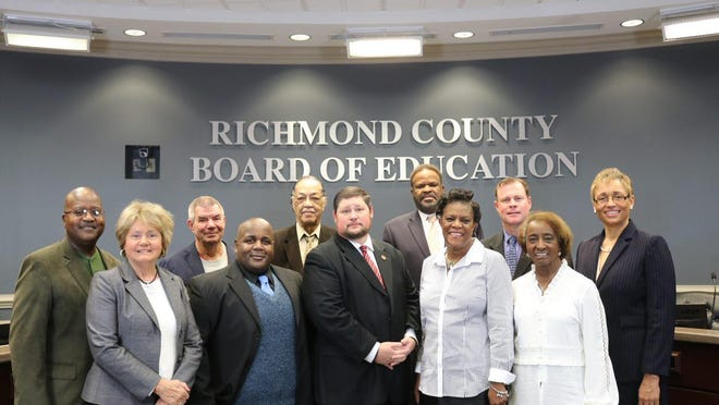 From left, Richmond County Board of Education trustees A.K. Hasan, Helen Minchew, Walter Eubanks, Charlie Hannah, Marion Barnes, Jimmy Atkins, Wayne Frazier, Venus Cain, Charlie Walker and Patsy Scott stand with former Superintendent Angela Pringle in 2018 after electing Atkins and Cain the board's president and vice president.
