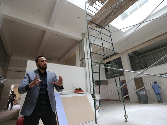 "Stanton House General Manager Aaron Rodriguez talks about the restaurant and bar at the new downtown boutique hotel.  A giant atrium-like structure, or ""light well"" is above him."