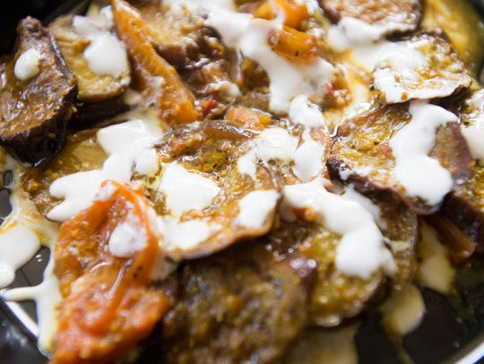 Burrani, an eggplant dish with sauce, is served at