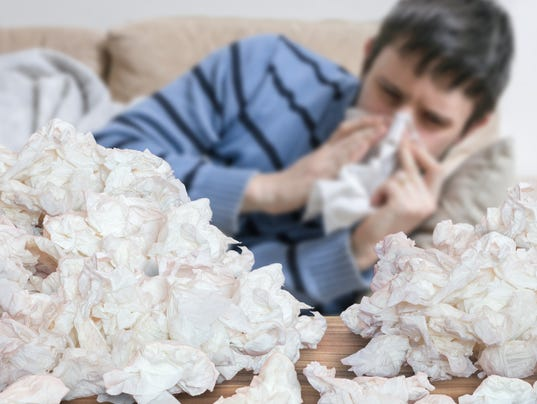 Funny sick man who has flu blowing nose with tissues