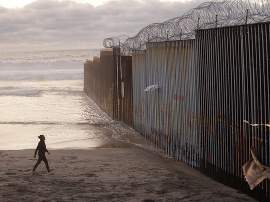 In this Jan. 9, 2019, photo, a woman walks on the beach next to the border wall topped with razor wire in Tijuana, Mexico. Congressional negotiators reached agreement to prevent a government shutdown and finance construction of new barriers along the U.S.-Mexico border, overcoming a late-stage hang-up over immigration enforcement issues that had threatened to scuttle the talks.