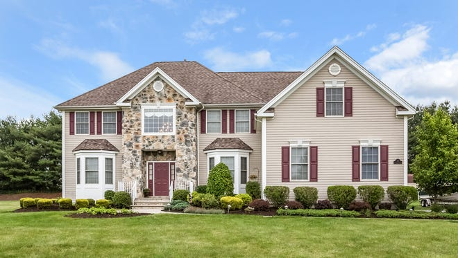 This four-bedroom Colonial has an open floor plan, an eat-in granite kitchen with a center island and a three-car garage.