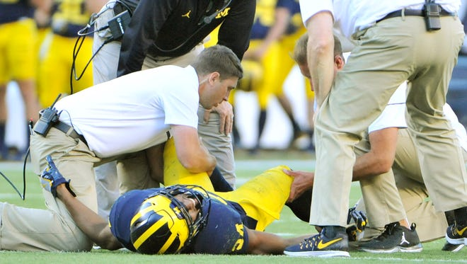 Michigan staff and head coach Jim Harbaugh check on corner back Jeremy Clark after an injury in the fourth quarter.