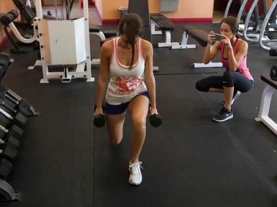Danielle Inzano, right, takes a photo of her twin sister Deanna while she does lunges. The two have more than 100,000 combined followers on instagram and more than 70,000 combines twitter followers.