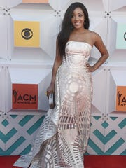 "Mickey Guyton poses on the red carpet at the 51st Academy of Country Music Awards in 2016. Guyton will sing ""I'm Standing with You"" with Carrie Underwood, Chrissy Metz, Lauren Alaina, and Maddie & Tae on Sunday's ACM Awards."