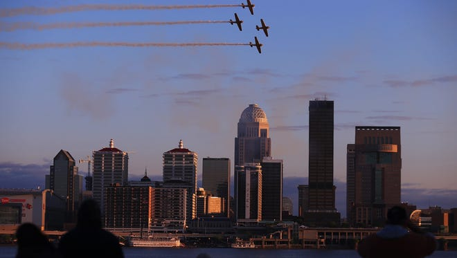 Before the start of the fireworks at Thunder Over Louisville, plane fly above the Ohio River as the sun sets.