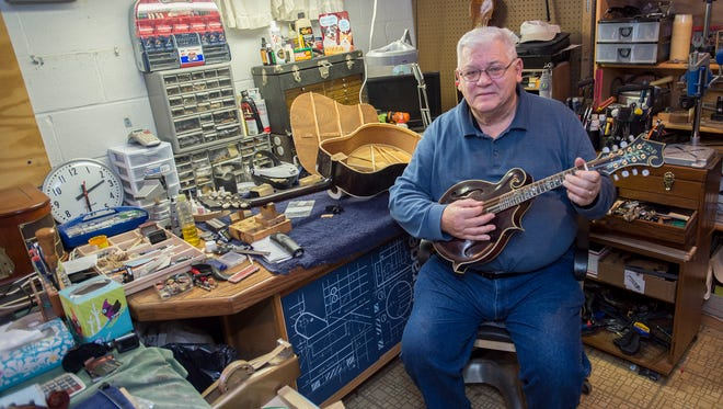 Ken Pugh sits inside of his shop holding a mandolin, that he had built, on Monday, Jan.18, 2015 in Waynesboro, Pa. Pugh repairs and builds violins, guitar and other string acoustic instruments.