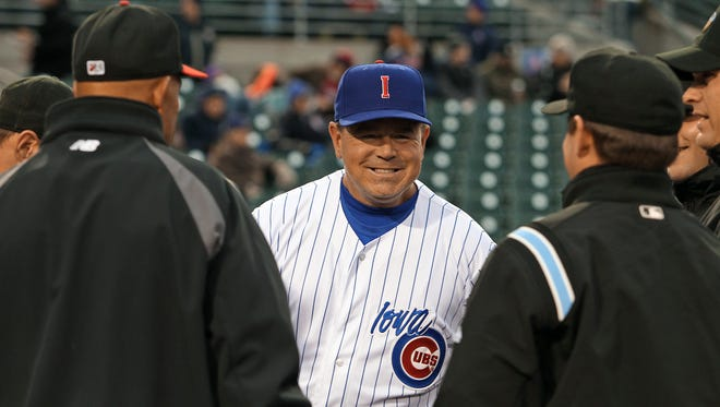 Iowa Cubs' manager Marty Pevey, center, talked with the umpiring crew and Albuquerque Isotopes' manager Lorenzo Bundy, left, during the line up exchage at the I-Cubs' home opener at Principal Park on Friday night April 12th, 2013.