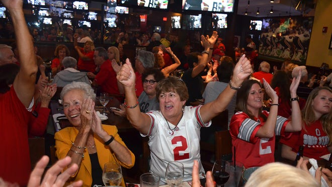 Naples Buckeye club members including Kay Barton, center, cheer the Buckeyes' first touchdown. Hundreds of Ohio State fans, and a few Oregon supporters, packed Bokamper's Sports Bar Monday evening for the first College Football Playoff National Championship game. Lance Shearer/Special to the Daily News