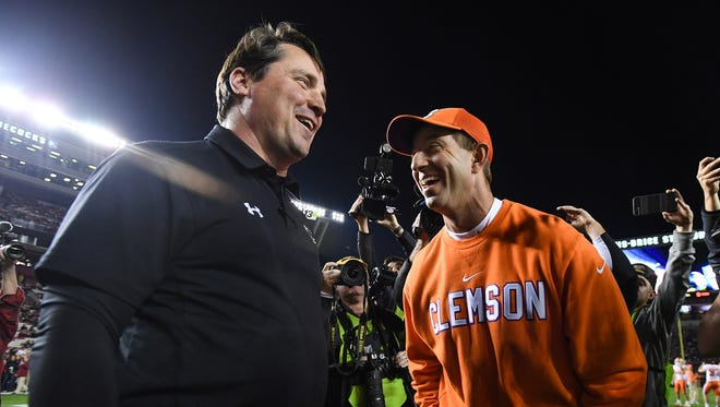 South Carolina head coach Will Muschamp, left,  meets with Clemson head coach Dabo Swinney during pre-game on Saturday, November 25, 2017 at Carolina's Williams Brice Stadium.