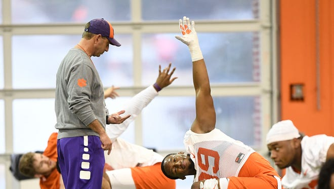 Clemson head coach Dabo Swinney talks with defensive lineman Clelin Ferrell (99) during the Tigers opening day of spring practice on Wednesday, February 28, 2018.