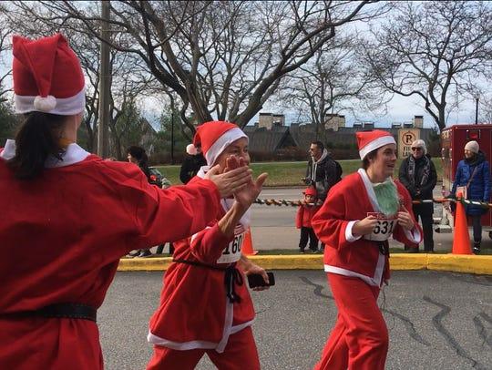 Runners in the annual Ri Ra Santa 5K get high-fives