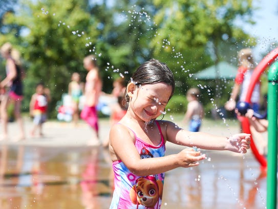 Avery Lyman cools off in the splash pad at Riverfront