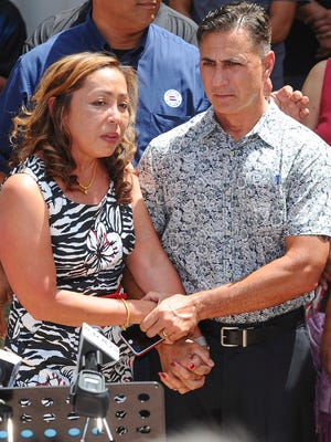 Walter Denton and his wfie, Shirley, clasp their hands together during a press conference June 7, 2016, outside the Dulce Nombre de Maria Cathedral-Basilica's pastoral center in Hagatna, Guam.