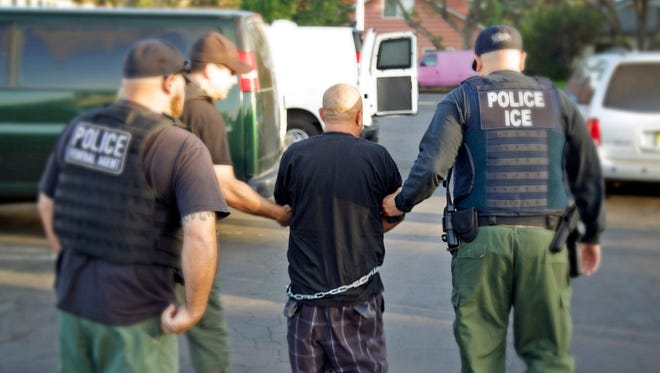 In this Oct. 14, 2014 photo, agents take a person into custody during an immigration sweep in Ontario, California.