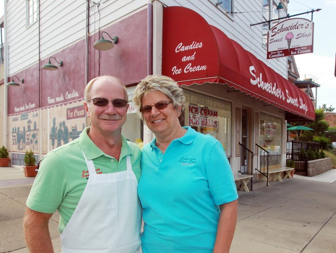 Jack and Kathy Schneider, owners of Schneider's Sweet Shop in Bellevue, outside their business.  The shop, which Jack's  father founded in 1939, is celebrating its 75th anniversary Aug. 16 with an all day party.