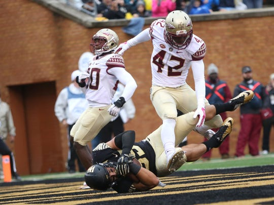 FSU's Lamarcus Brutus jumps over Wake Forest's Chuck Wade as he slides into the endzone for a touchdown at BB&T Field on Saturday.