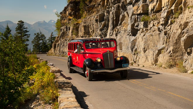 A Red bus navigates Going-to-the-Sun Road in Glacier National Park.