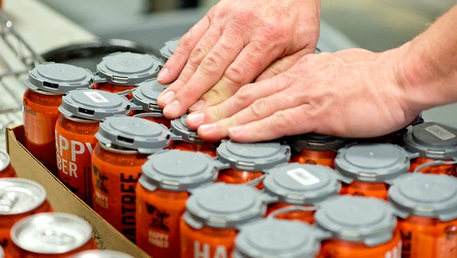 MadTree Brewing offered an inside look at its canning process and new tasting room. Protective caps are snapped onto freshly canned Happy Amber beer.