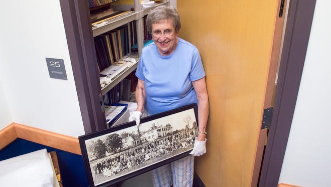 Joan Bowen holds an old photo in her hands while standing in front of a room, where most of Chambersburg Area School District's yearbooks, photos, newspaper clipping and other historical memorabilia are stored, on Monday, August 22, 2016 at the district's administration building. Bowen is a CASD historian.