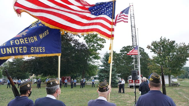 Flags are on display as North Kingstown holds a 9/11 memorial ceremony at the North Kingstown Town Beach on Friday.